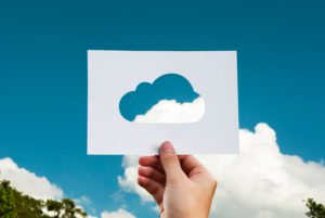 Cloud native enablement portrayed by a cloud cutout in paper held up to the sky to a cloud