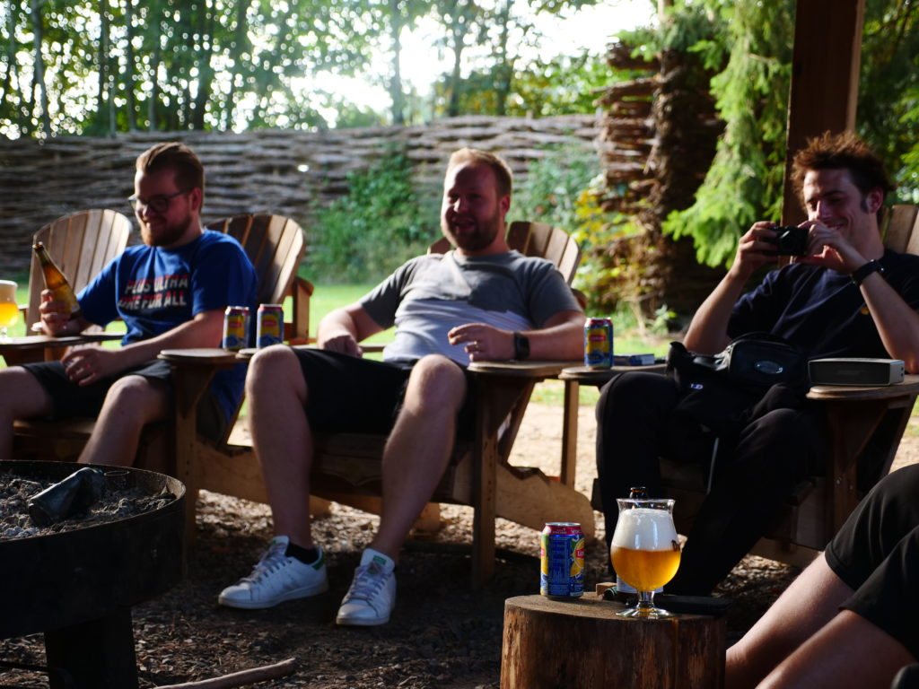 Three people with beers next to campfire during the ToThePoint Teambuilding weekend at Les Ondes
