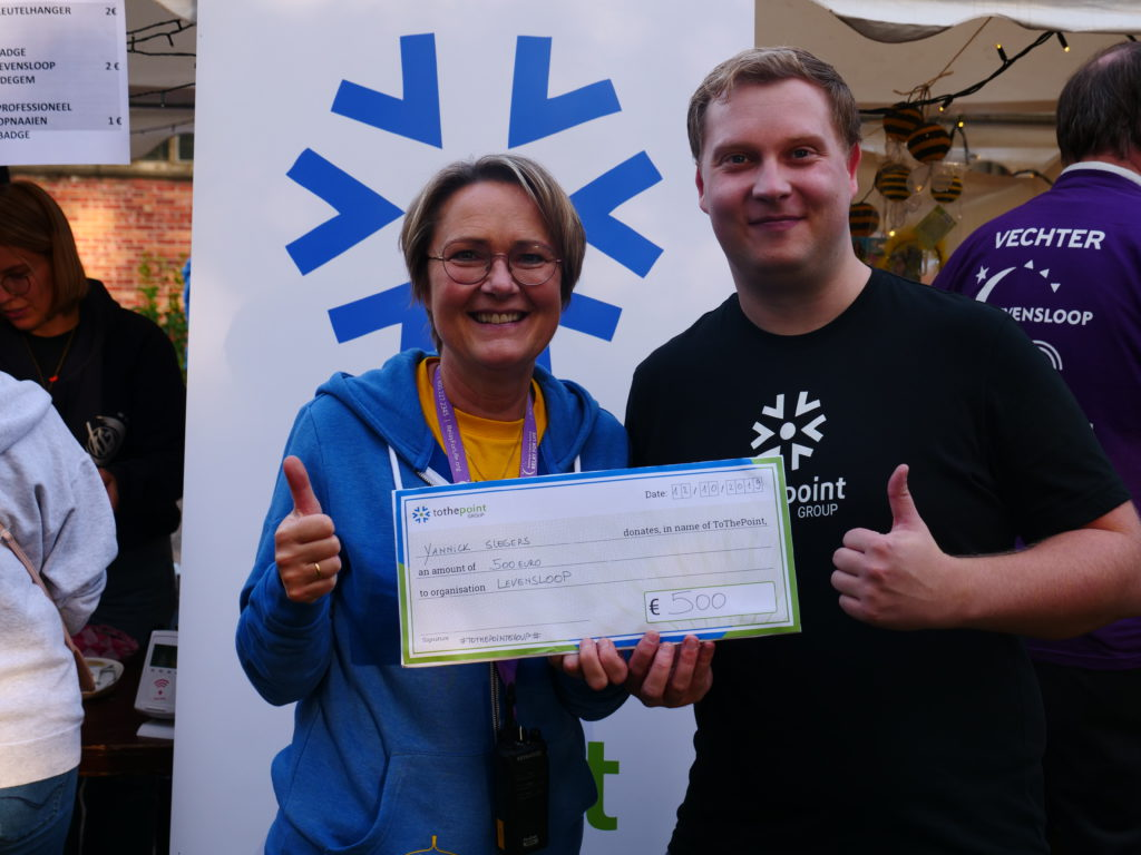 Evolutionary Architect Yannick Slegers offering a check of €500 to Levensloop Edegem through tothepoint's charitable signing fee program.
